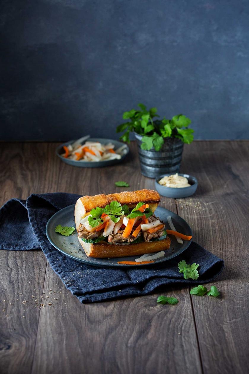 Bánh mì auf einem Teller auf einem gedeckten Tisch.