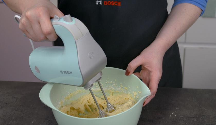 Der Teig von dem Birnenkuchen mit Knusperkruste wird in einer Rührschüssel mit einem Handmixer zubereitet.