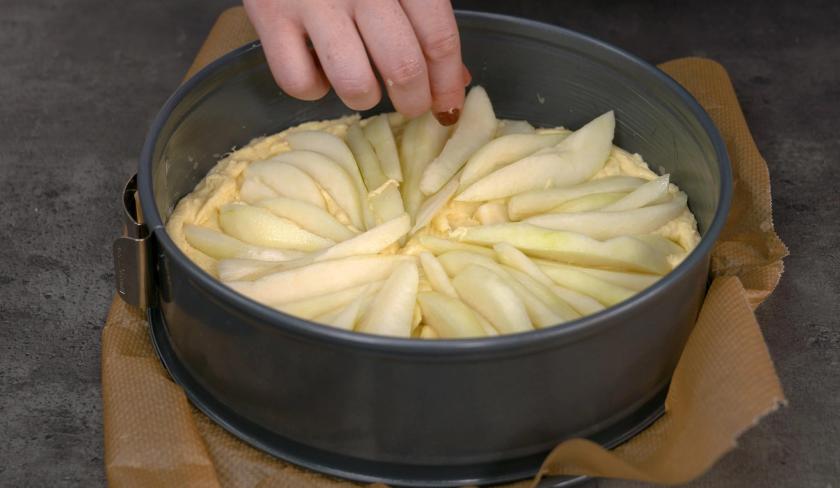 Für den Birnenkuchen mit Knusperkruste wird das Obst auf dem Teig verteilt.