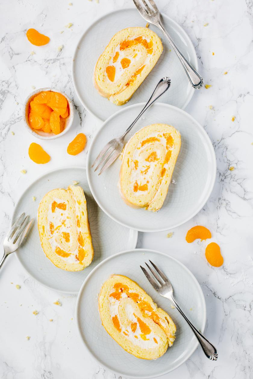 Vier Stücke Biskuitrolle mit Mandarinen auf weißen Tellern.