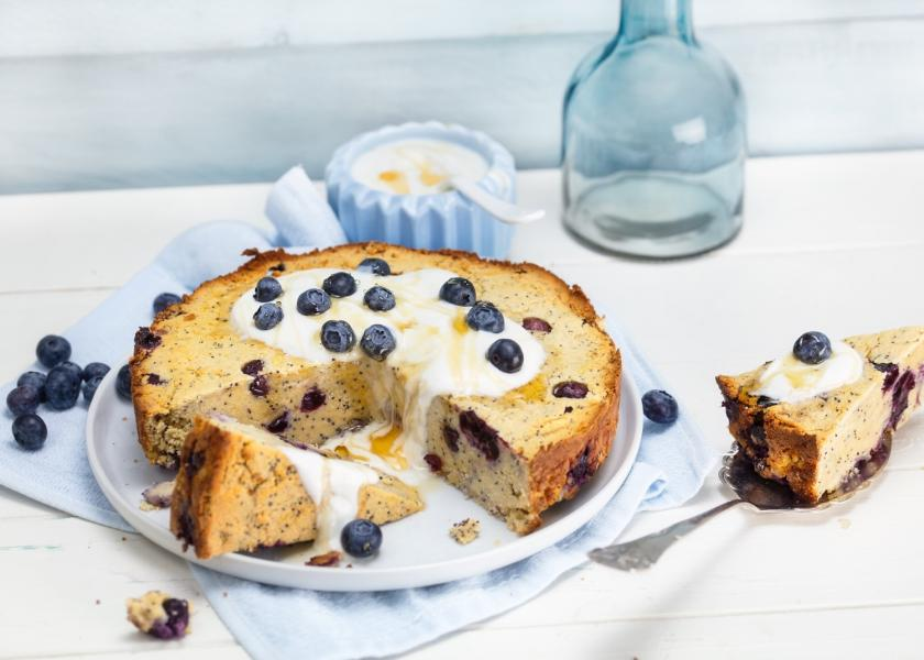 Angeschnittener Blaubeer-Mandelkuchen mit Joghurt.