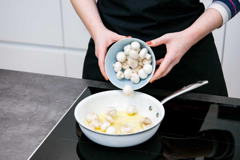 Für Boeuf Bourguignon werden Pilze in einer Pfanne angebraten.