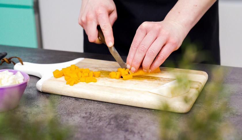 Für die Bolognese-Törtchen mit Knusperteig werden Möhren auf einem Holzbrett gewürfelt.