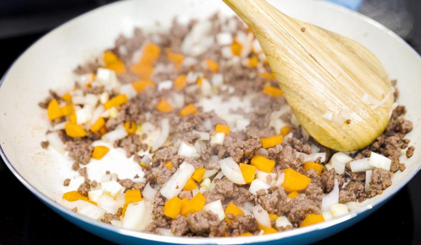 Für die Bolognese-Törtchen mit Knusperteig wird Hackfleisch mit Möhre in einer Pfanne angebraten.