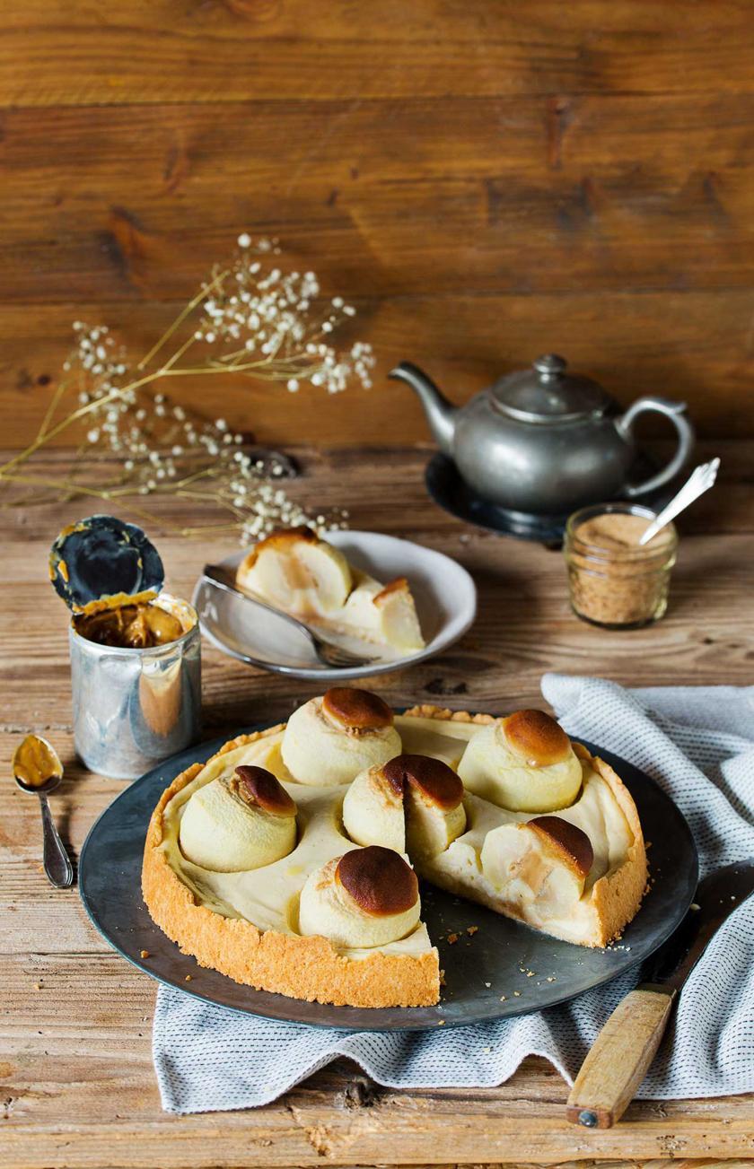 Bratapfel-Käsekuchen angeschnitten auf einem gedeckten Tisch.
