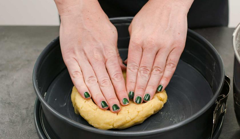 Für den Bratapfel-Käsekuchen wird Mürbeteig in der Form verteilt.