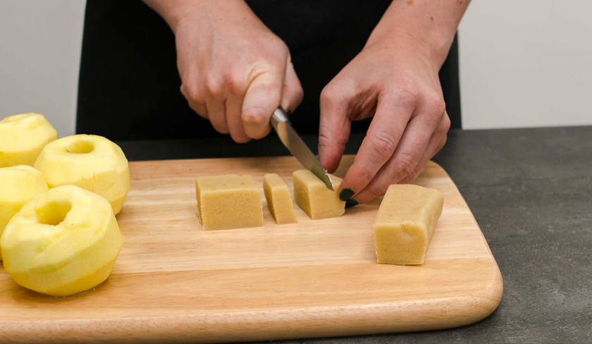 Für den Bratapfel-Käsekuchen wird Marzipan in Stücke geschnitten.