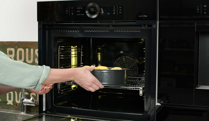 Der Bratapfel-Käsekuchen wird in den Ofen gegeben.