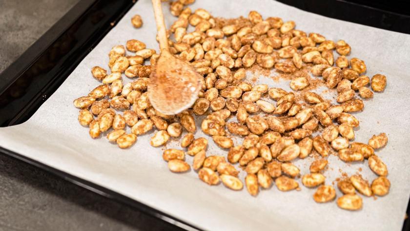 Gebrannte Mandeln werden auf einem Blech mit einem Kochlöffel verteilt.