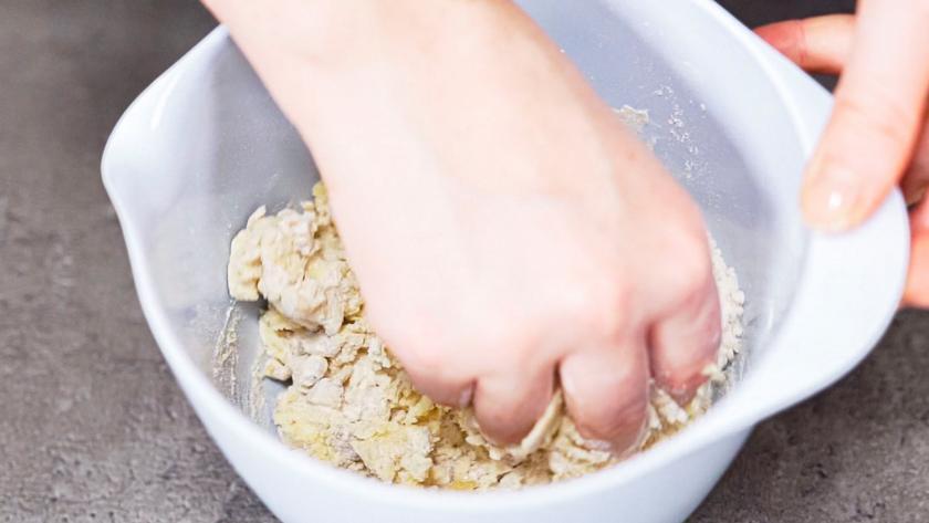 Der teig für die Streusel wird in einer Schüssel geknetet.