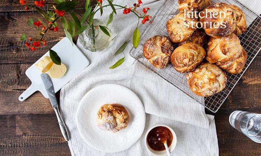 Mehrere Brioche-Knoten mit Mandeln und Puderzucker in einer Schale und auf einem Teller.