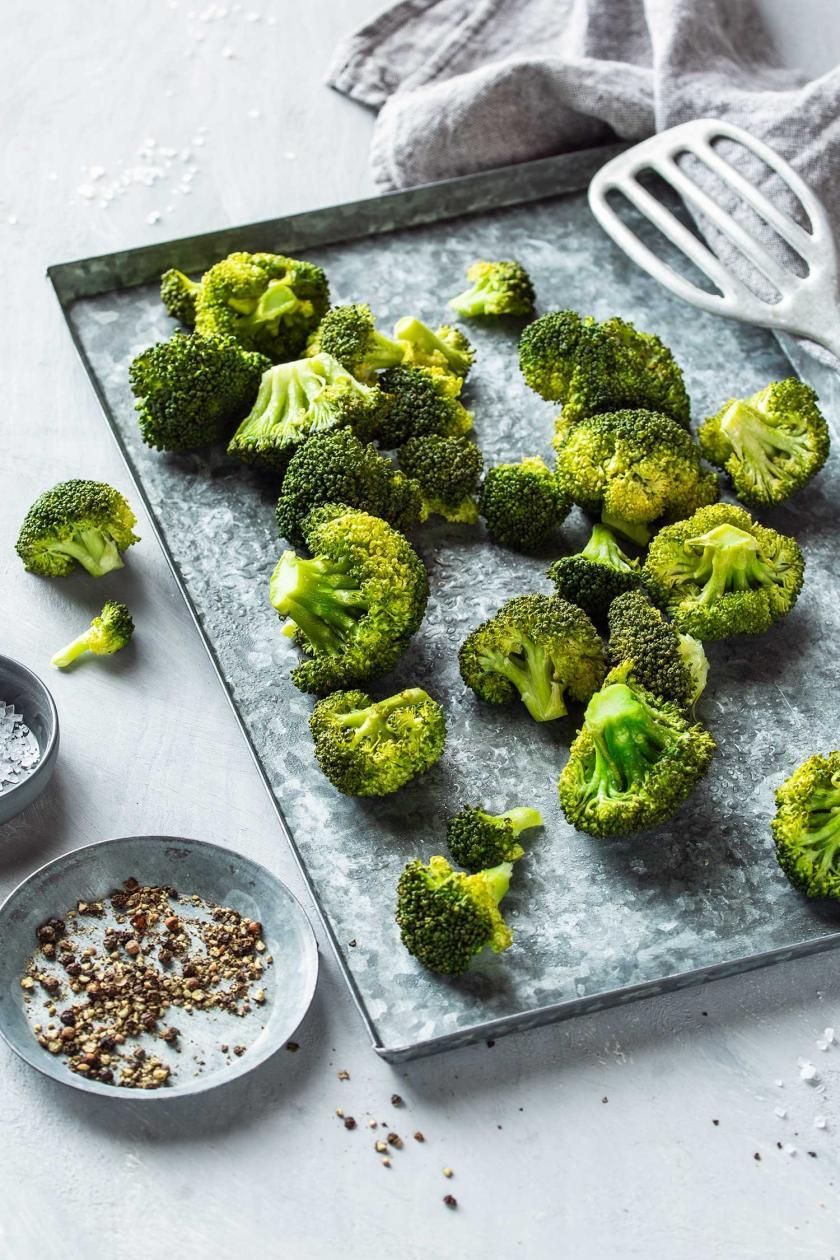 Brokkoli dampfgegart auf einem Blech verteilt, daneben Salz und Pfeffer.