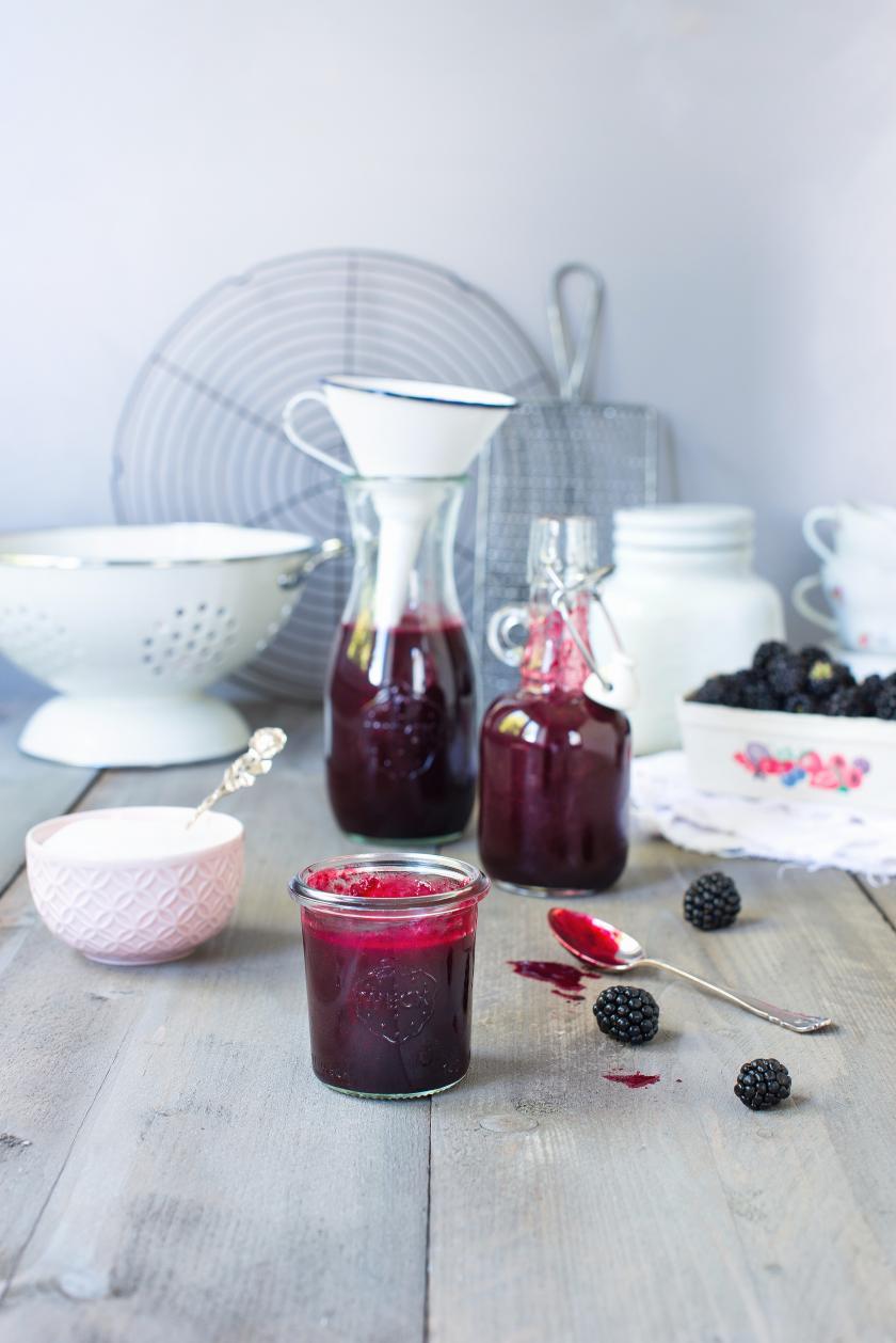 Ein Glas Brombeersirup steht auf einem Tisch mit einer Schale Zucker, einem Sieb und Brombeeren im Hintergrund.