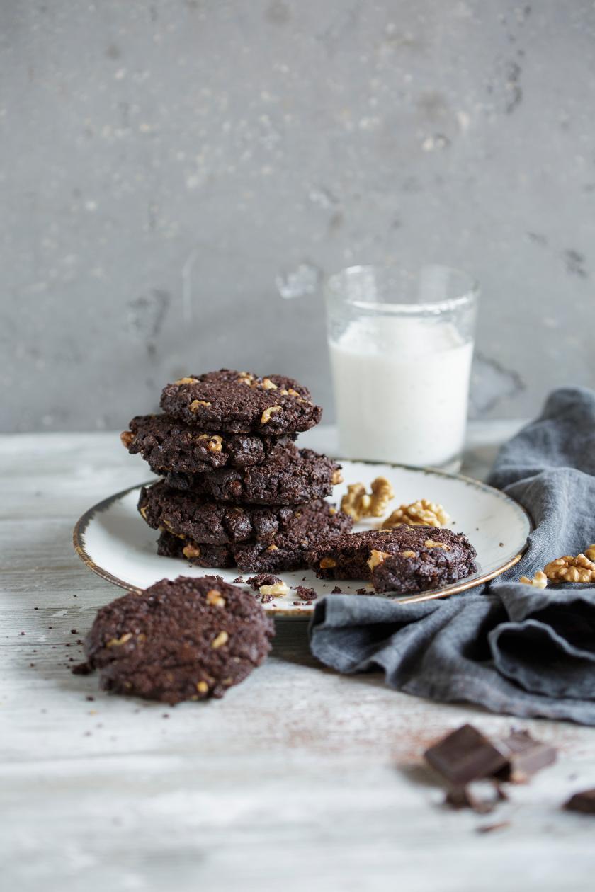 Mehrere Brownie-Cookies auf einem Teller, daneben ein Glas Milch.
