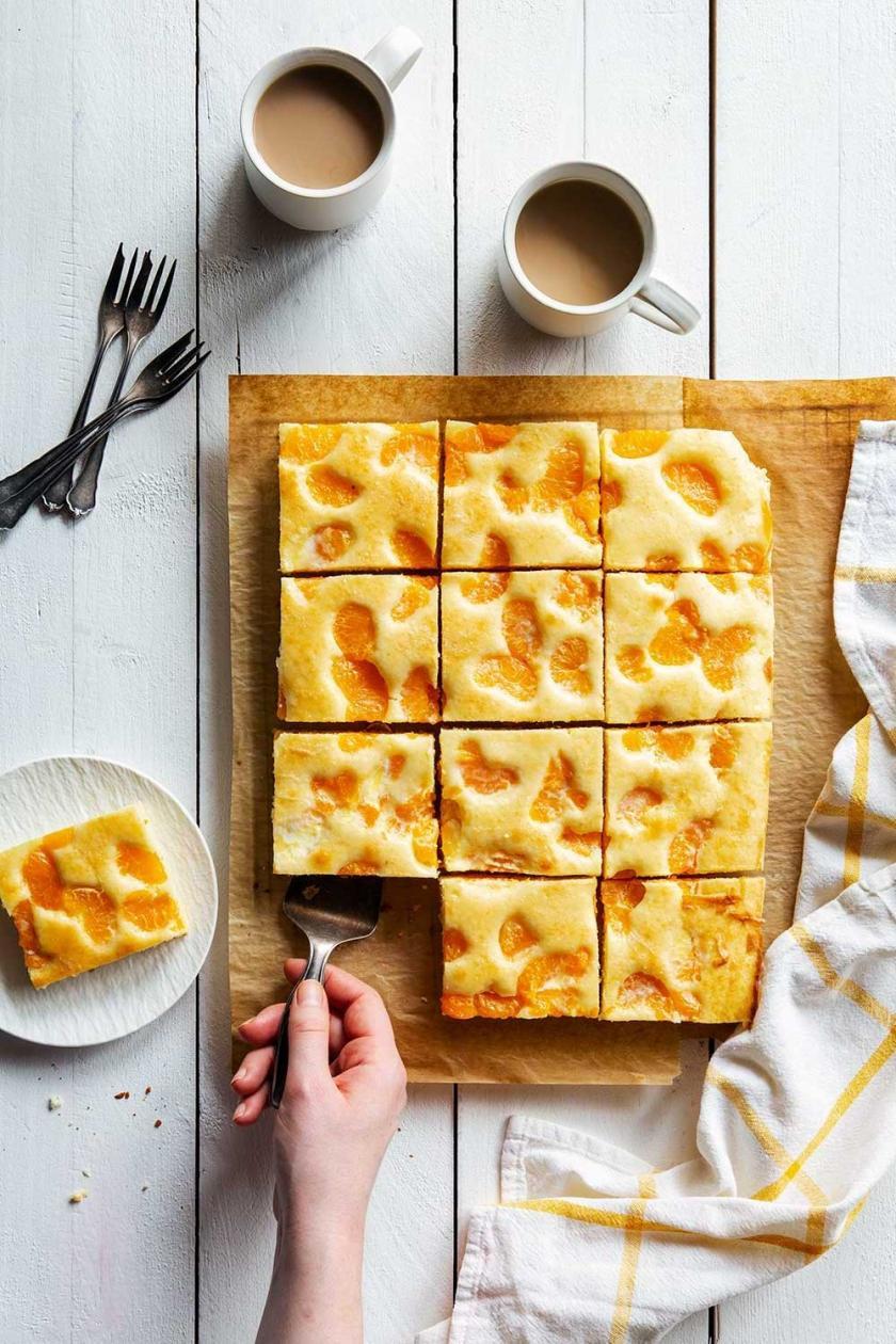 Hand nimmt ein Stück vom Buttermilchkuchen mit Hand weg.