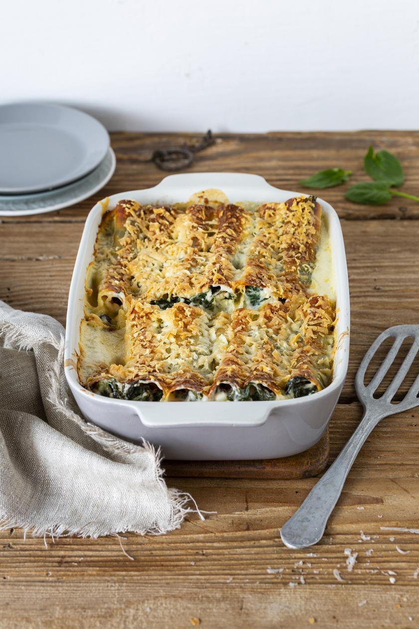 Cannelloni mit Spinat und Feta in einer Auflaufform geschichtet.