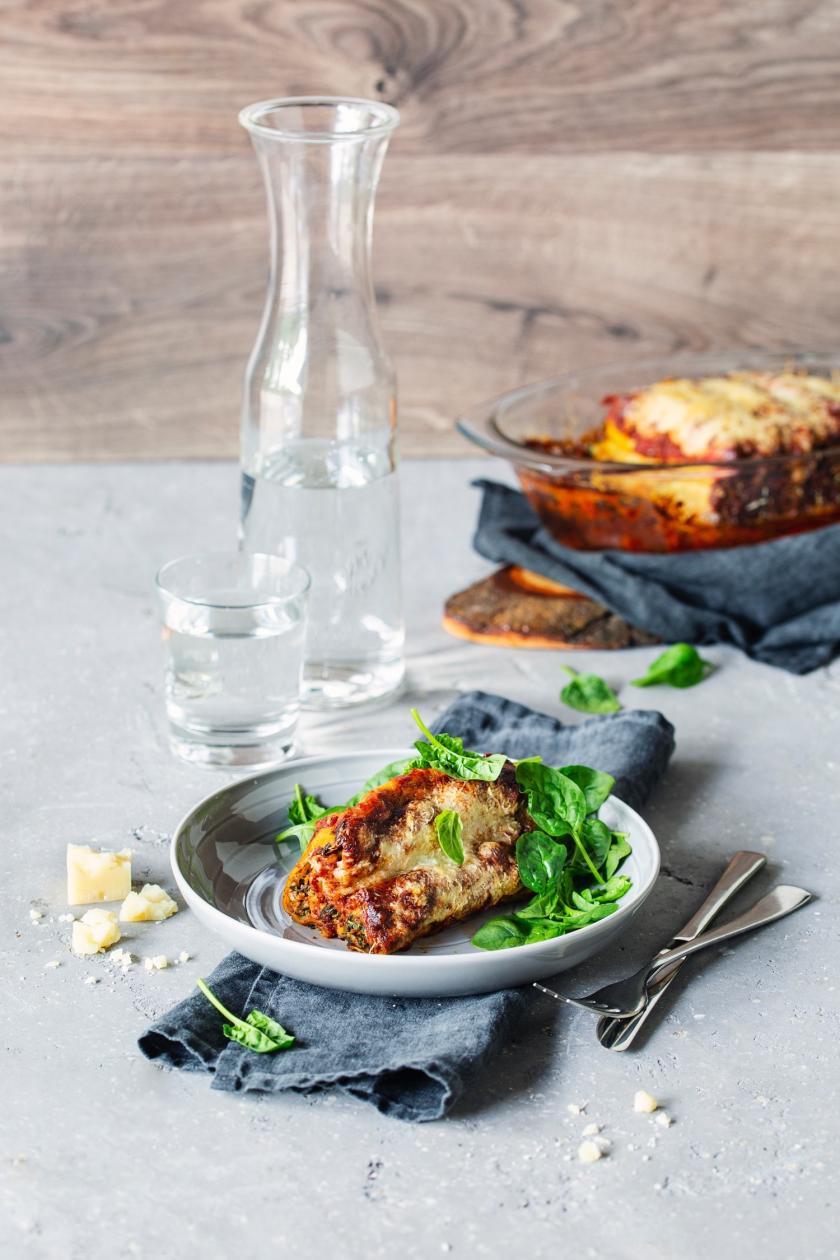 Auflaufform und Teller mit Cannelloni mit Spinat-Ricotta-Füllung.