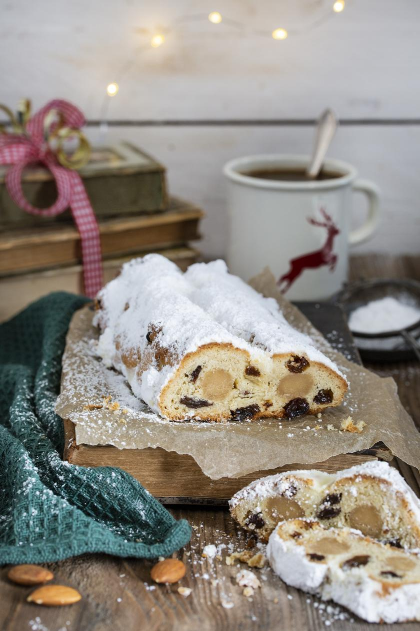 Christstollen mit Marzipan auf einem weihnachtlichen Tisch auf einemm Holzbrett und angeschnitten.