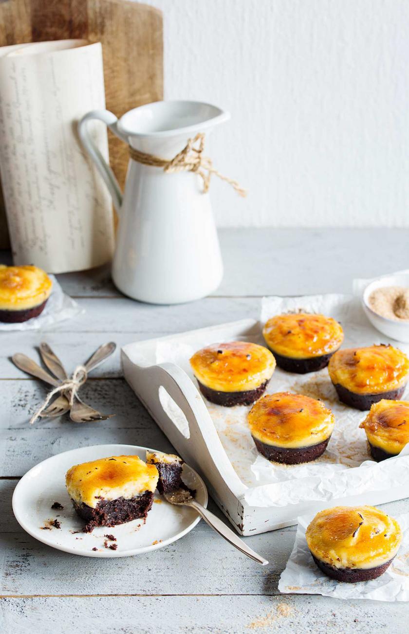 Mehrere Crème Brulée Brownie Törtchen auf einem Tablett. Im Vordergrund eins davon auf einem Teller.