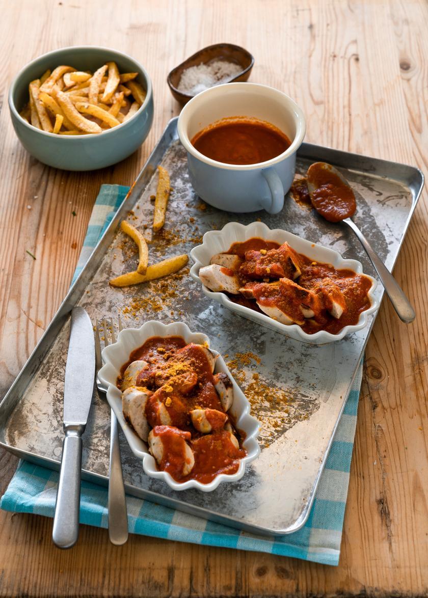 Currywurst mit Pommes auf einem Tablett. Daneben ein Becher mit Currywurstsoße.