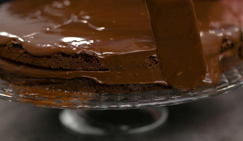 Der Death by Chocolate wird rundherum mit Ganache eingestrichen.