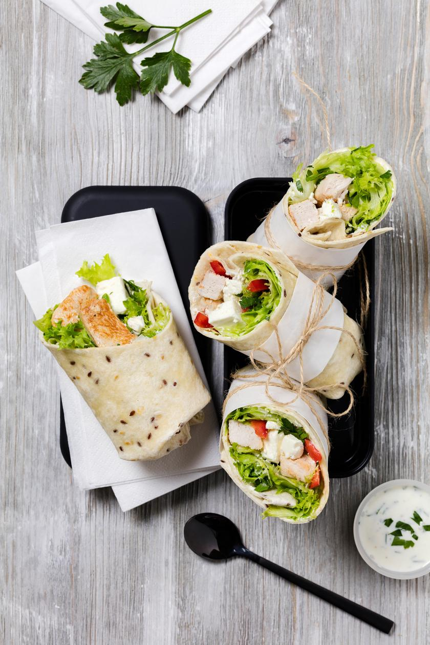 Wrap mit Hähnchen und Salat Meal Prep aufgeschnitten in einer Dose liegend.