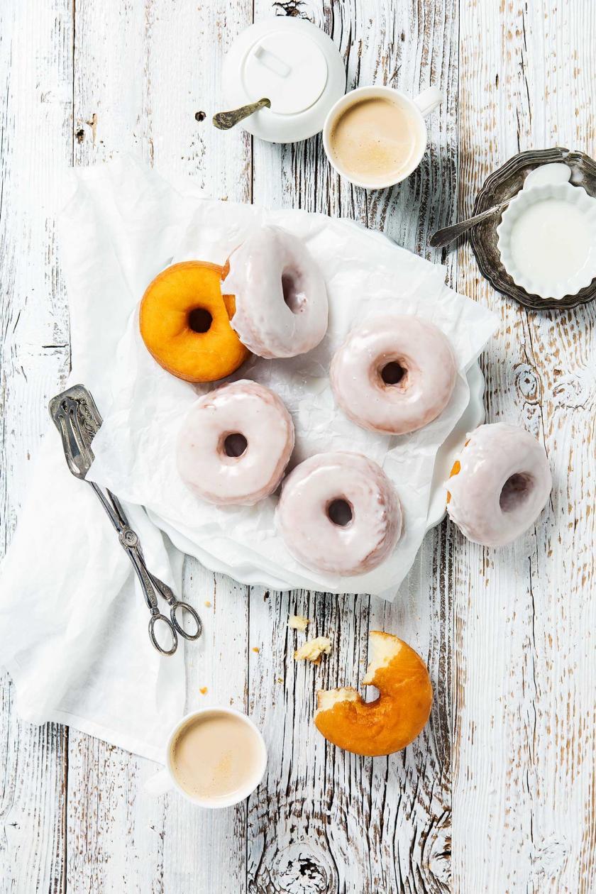Mehrere Donuts glasiert und unglasiert auf einem Teller.