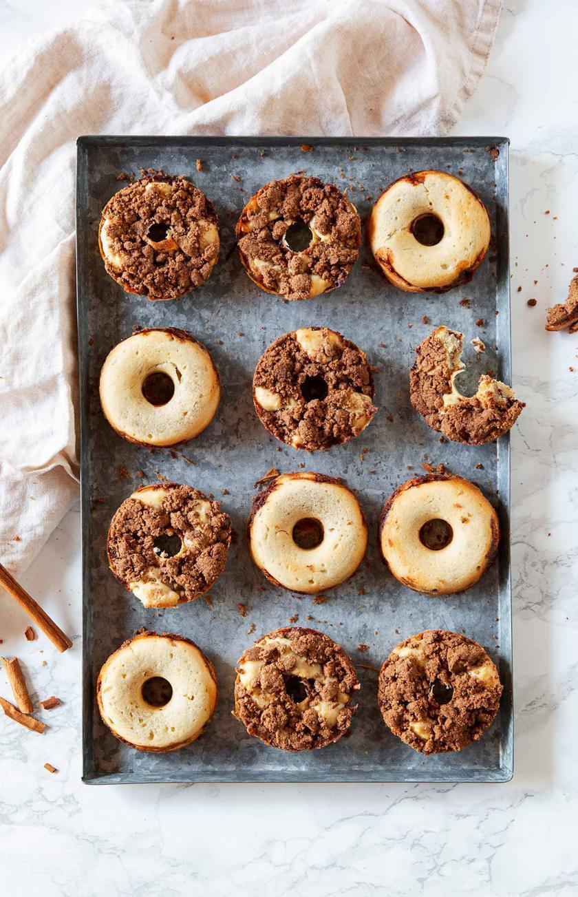 Viele Donuts mit Zimtstreuseln auf einem Blech.