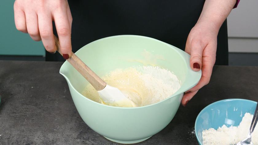 Die trockenen Zutaten für den Eierlikör Drip Cake mit weißer Schokolade werden unter die Eimasse gehoben.