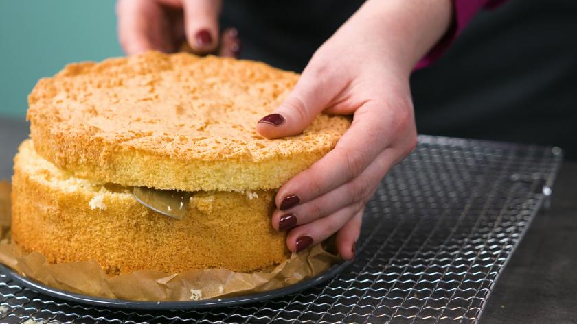 Der Biskuitboden für den Eierlikör Drip Cake mit weißer Schokolade wird waagerecht durchgeschnitten.