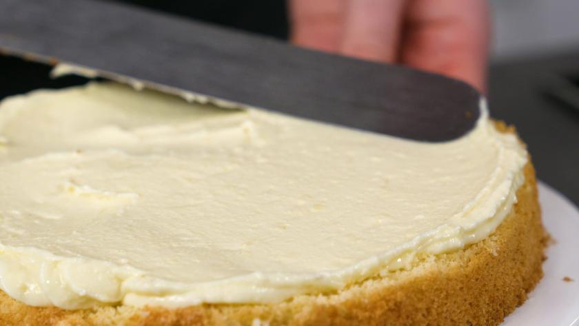 Der Boden des Eierlikör Drip Cake mit weißer Schokolade wird mit Creme bestrichen.