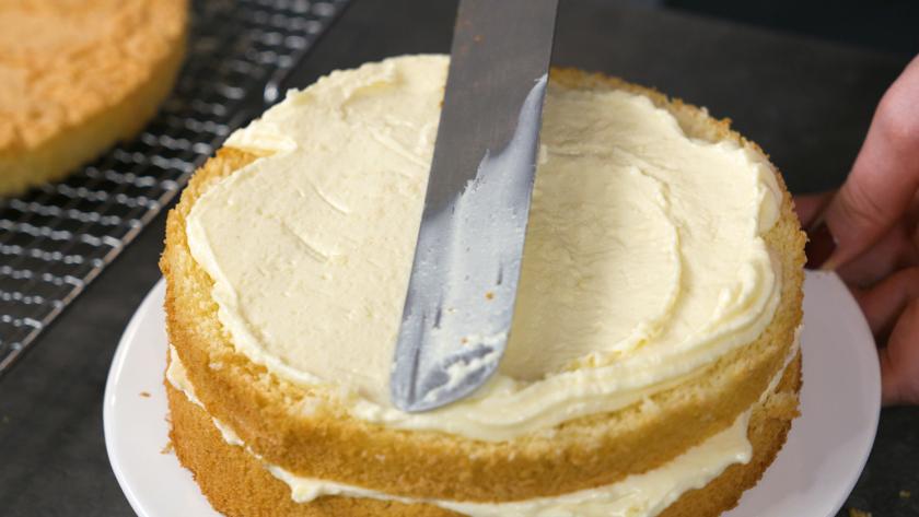 Boden und Creme werden für den Eierlikör Drip Cake mit weißer Schokolade gestapelt und bestrichen.