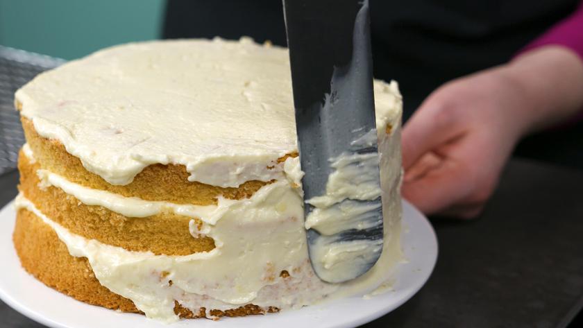 Der Biskuit für den Eierlikör Drip Cake mit weißer Schokolade wird rundherum mit Creme eingestrichen.