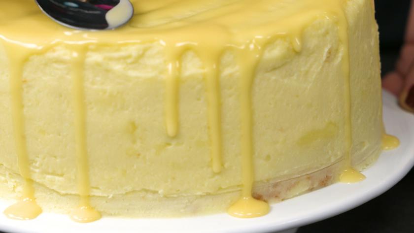 Der Eierlikör auf dem Eierlikör Drip Cake mit weißer Schokolade wird mit einem Löffel verteilt.