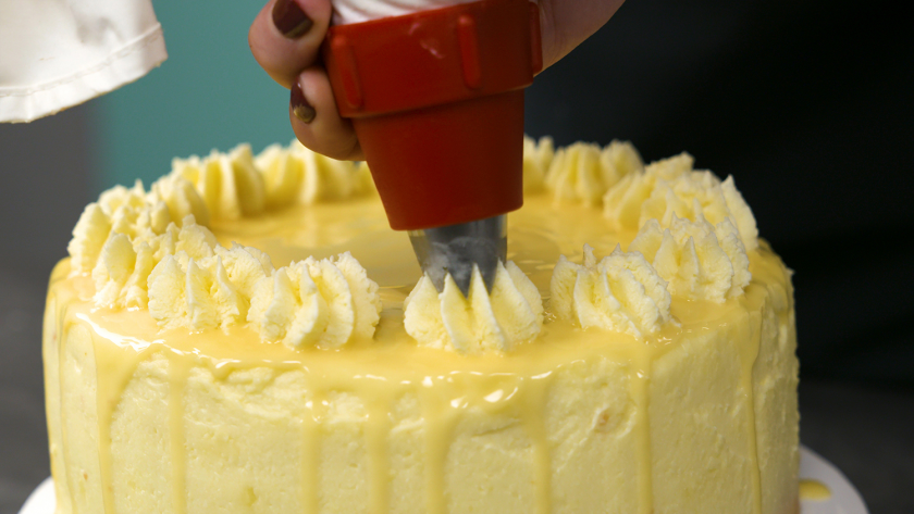 Der Eierlikör Drip Cake mit weißer Schokolade wird mit Cremetupfen verziert.