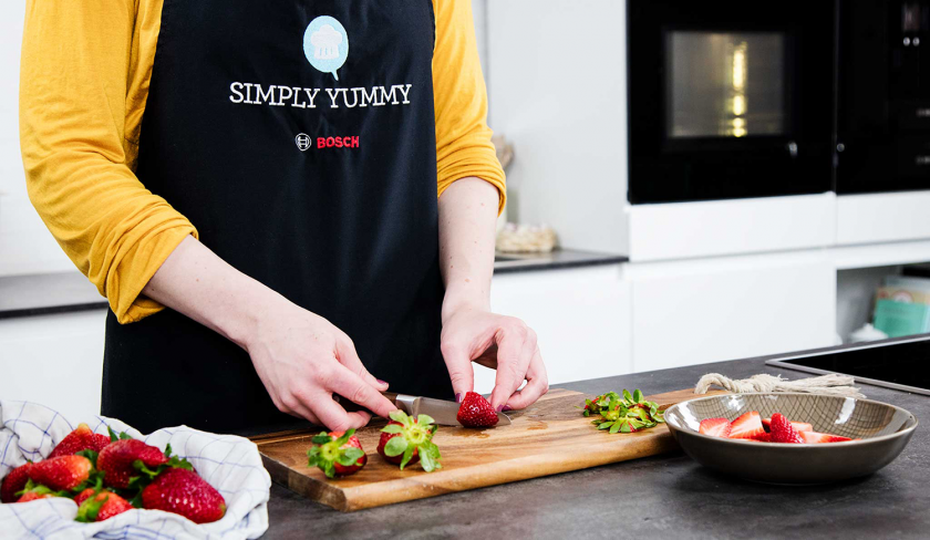 Erdbeeren für den Erdbeer-Rhabarber-Cobbler werden geschnitten.