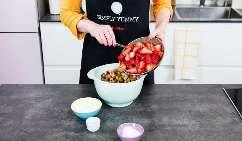 Erdbeeren für die Füllung des Erdbeer-Rhabarber-Cobblers werden zu Rhabarber in eine Schüssel gefüllt.