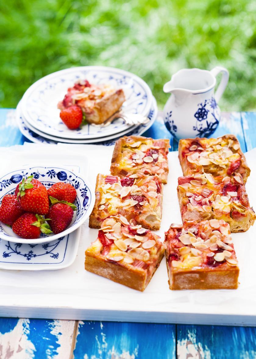 Mehrere Stücke Erdbeer-Rhabarber-Kuchen liegen auf einem weißen Brett auf einem gedeckten Kaffeetisch.