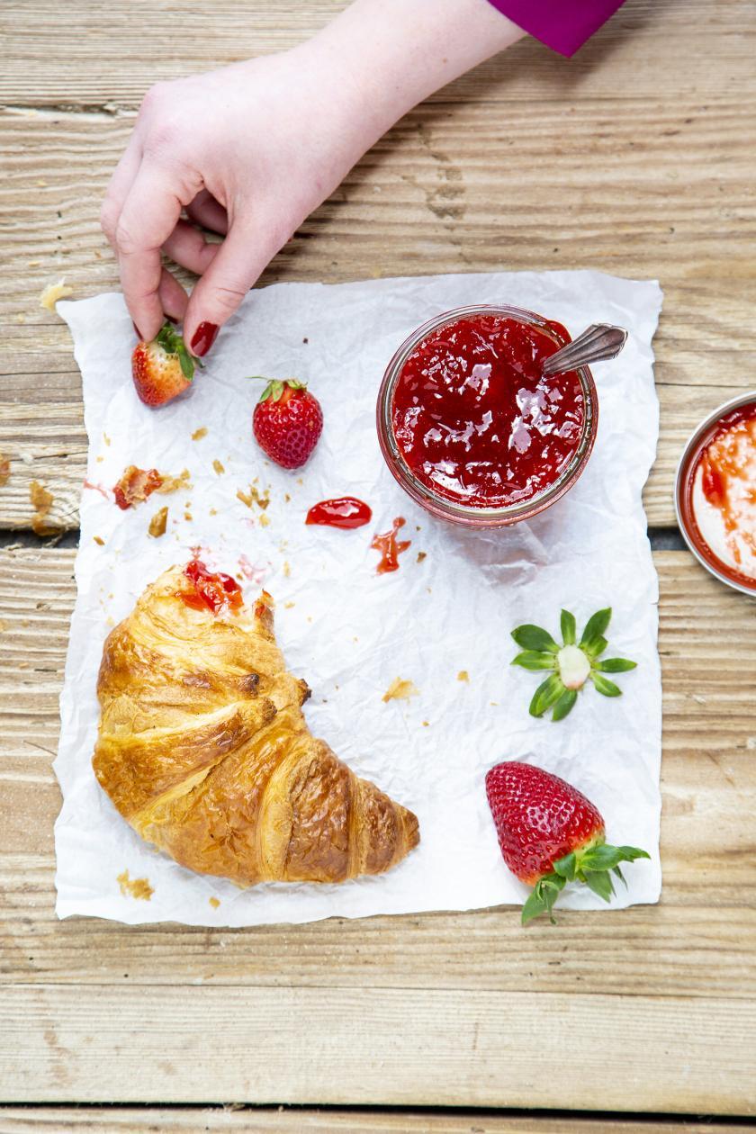 Erdbeermarmelade im Glas dazu ein abgebrochenes Croissant
