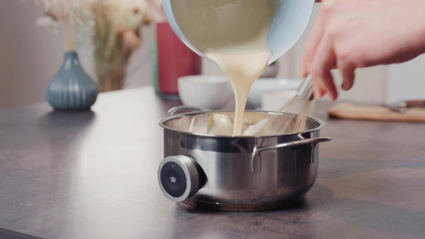 Eigelb-Stärke-Mischung wird in die heiße Milch eingerührt.