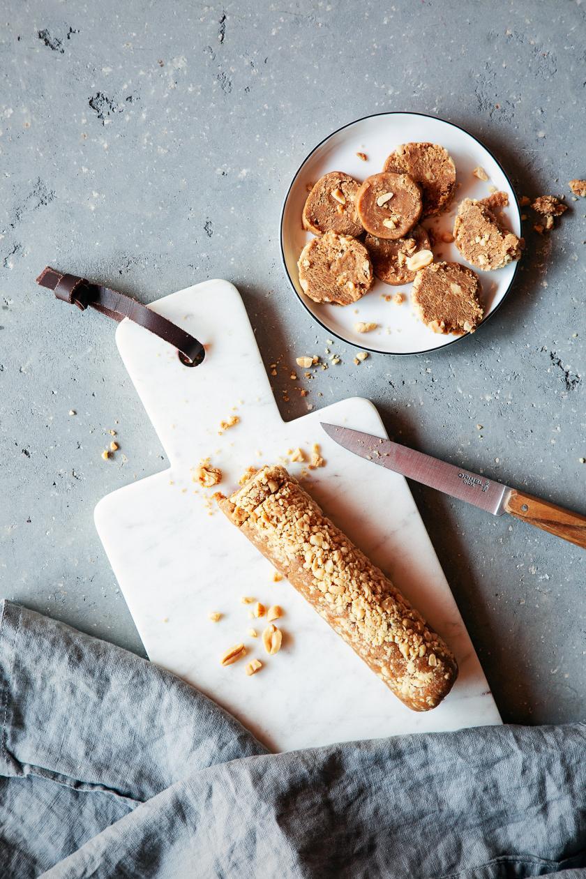 Erdnussbutterkekse ohne Backen zum Teil in Scheiben geschnitten auf einem Brett und Teller.