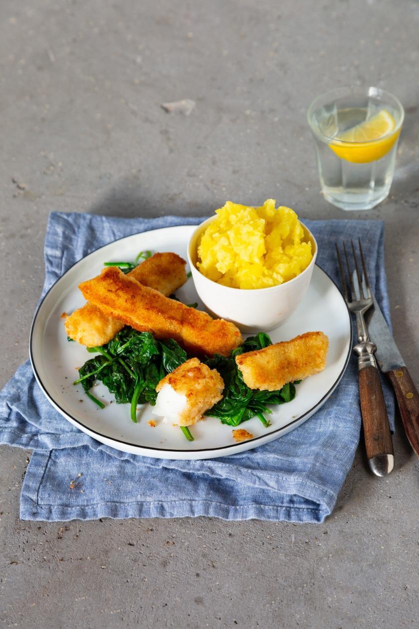 Fischstäbchen, Spinat und Kartoffelpüree auf Teller mit Wasserglas und Besteck