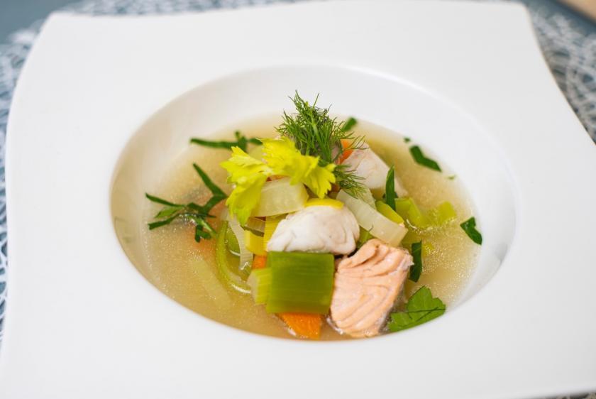 Fischsuppe mit Gemüse in weißem tiefen Teller.