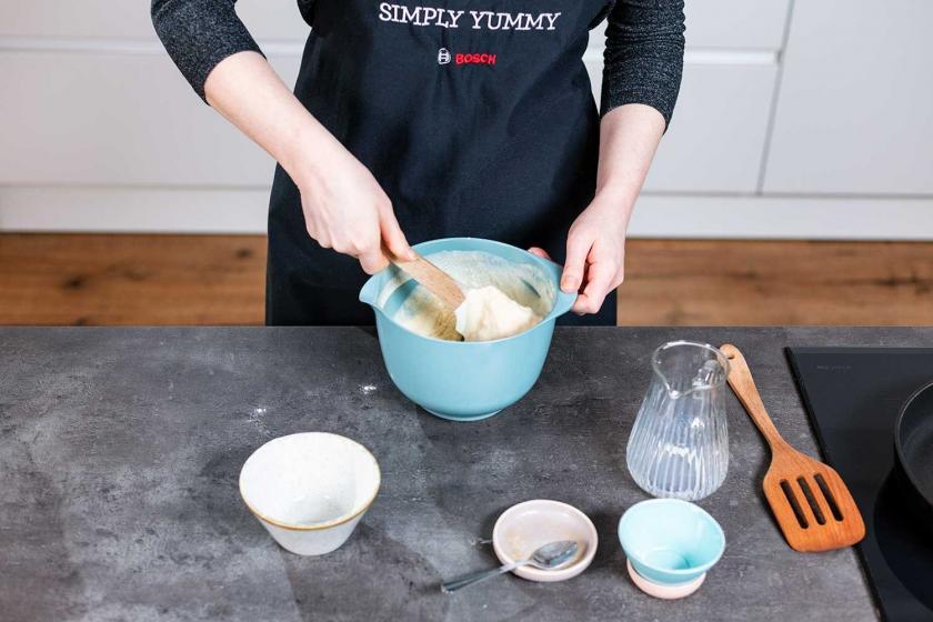 Der Teig für fluffige Pancakes wird per Hand mit einem Löffel verrührt.