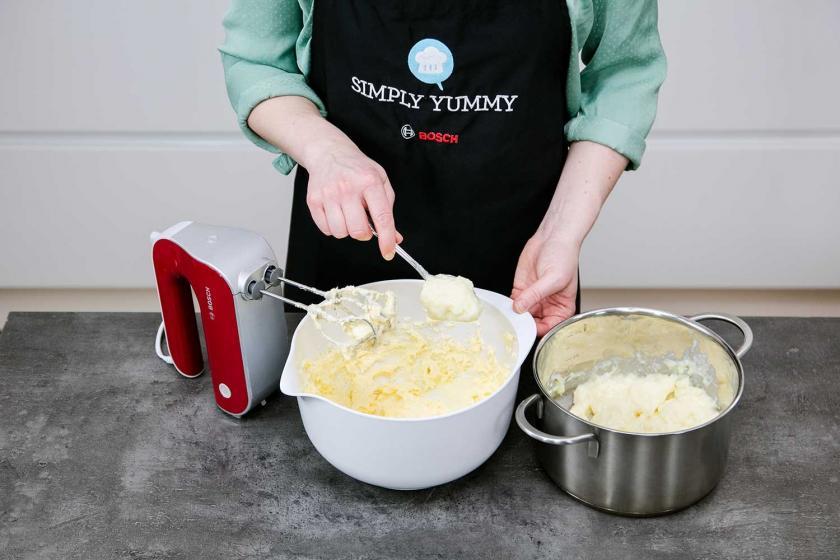 Für die Deko für den Frankfurter Kranz wird Buttercreme mit einem Löffel aus der Schüssel abgenommen.