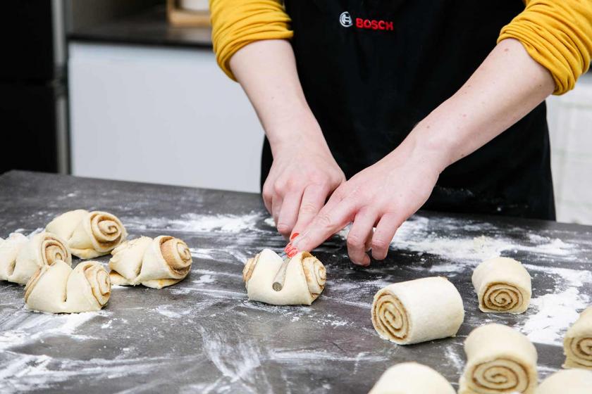 Die Franzbrötchen werden mit dem Stiel eines Kochlöffels geformt.