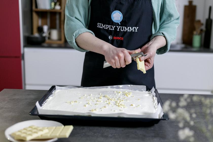 Weiße Schokolade wird in Raspel geschnitten und auf dem Frau Holle Kuchen verteilt.