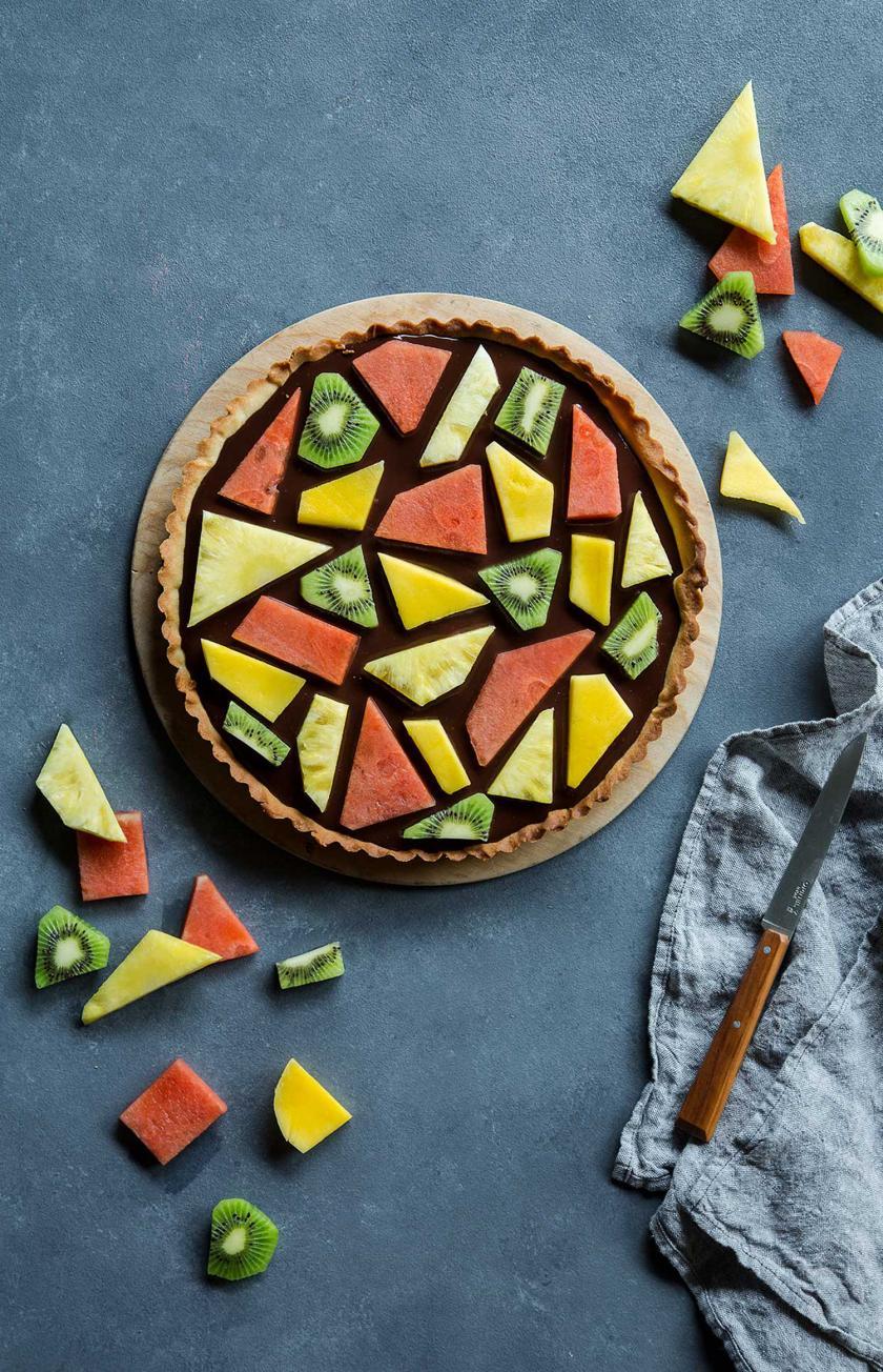 Fruchtiger Mosaik Kuchen auf einem Holzteller angerichtet. Obst drumherum.