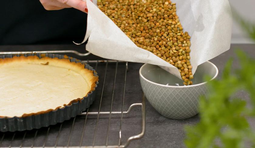 Die Erbsen vom Blindbacken werden vom Boden des fruchtiger Mosaik Kuchens genommen und in eine Schale gefüllt.