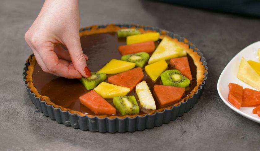 Die Obststücke werden auf der Ganache verteilt und ergeben fruchtiger Mosaik Kuchen.